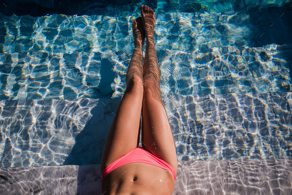 Female sexy tanned wet legs into water at pool. - Stock Photo - Images
