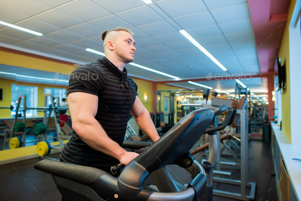 Attractive young muscular man while running on a treadmill in gym - Stock Photo - Images