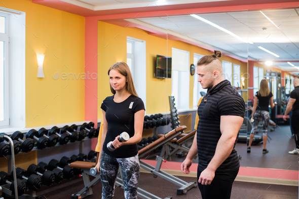 Woman with her personal fitness trainer in the gym exercising power gymnastics with a barbell - Stock Photo - Images