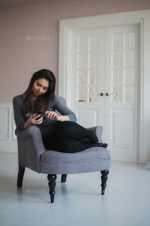 Smiling girl relaxing at home, she is connecting and social networking with her smartphone - Stock Photo - Images