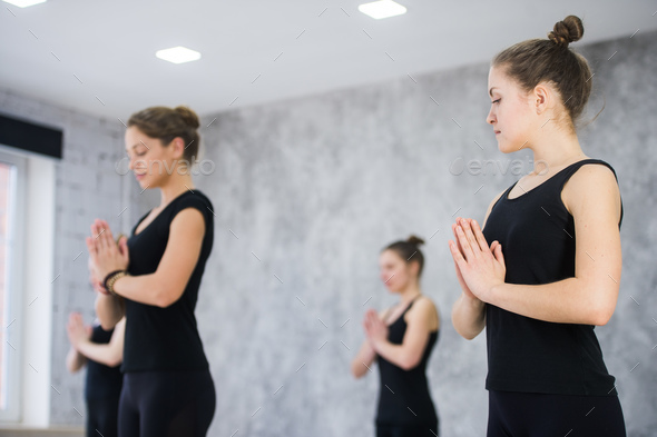Female trainer with class standing in namaste pose at yoga class - Stock Photo - Images