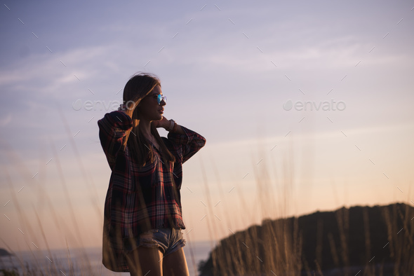 Hipster stylish woman traveler looking on a sea or ocean at the sunset - Stock Photo - Images