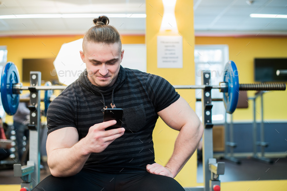 Young handsome man using phone while having exercise break in gym. - Stock Photo - Images