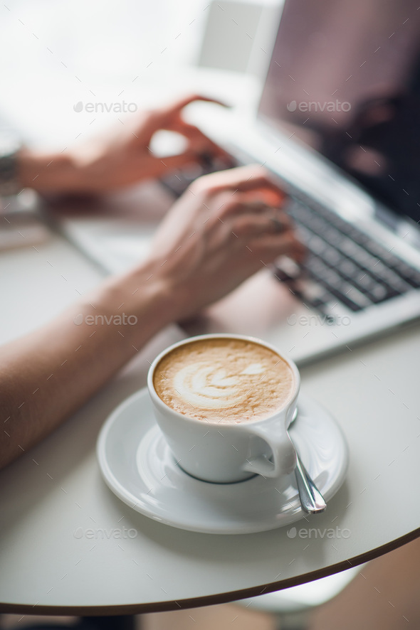 Woman using a laptop during a coffee break, hands close up. - Stock Photo - Images