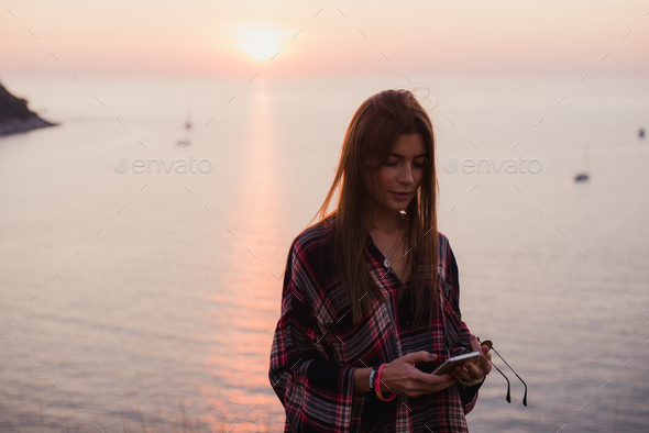 woman texting on smart phone on the beach during sunset - Stock Photo - Images