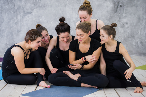 Smiling yogi girl exercising, having a break at class, group of friends watching on the phone - Stock Photo - Images