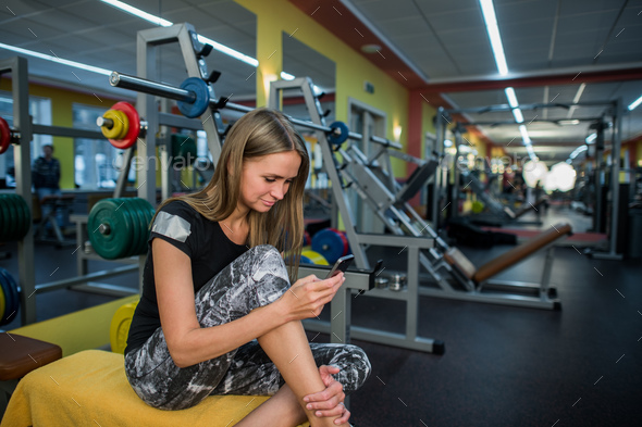 Young woman using phone in gym. - Stock Photo - Images