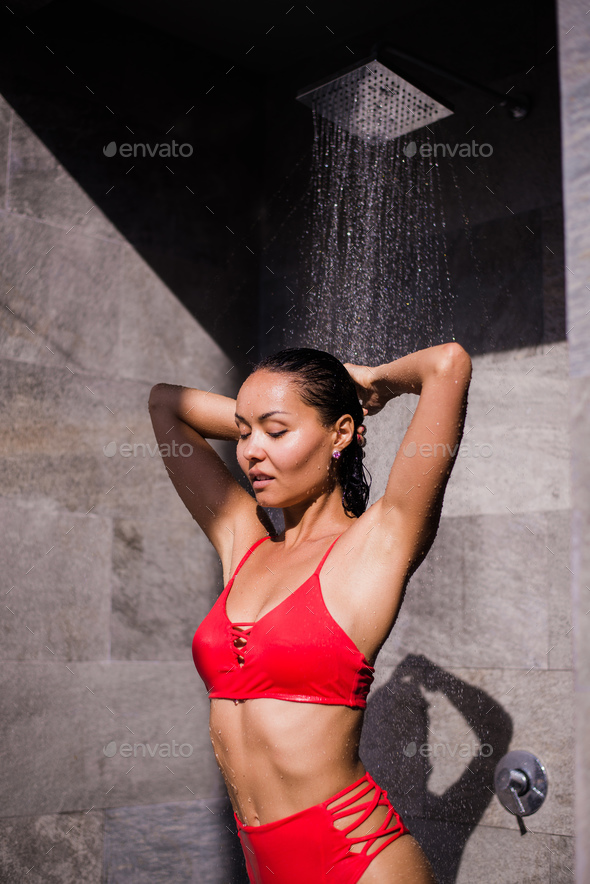A young sexy woman wearing red swimsuit showering outside at luxury hotel - Stock Photo - Images