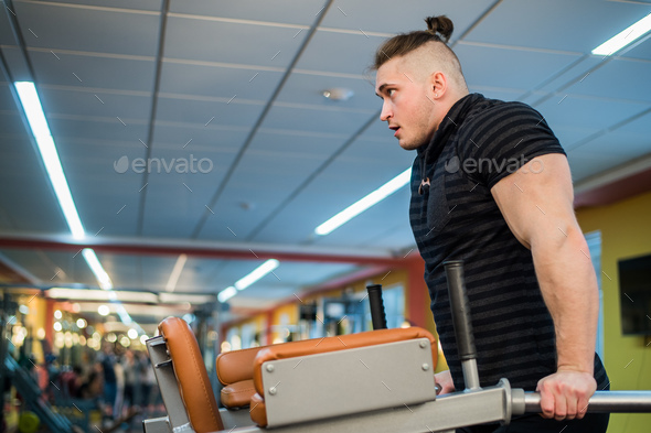 Focused man doing dips in the gym - Stock Photo - Images