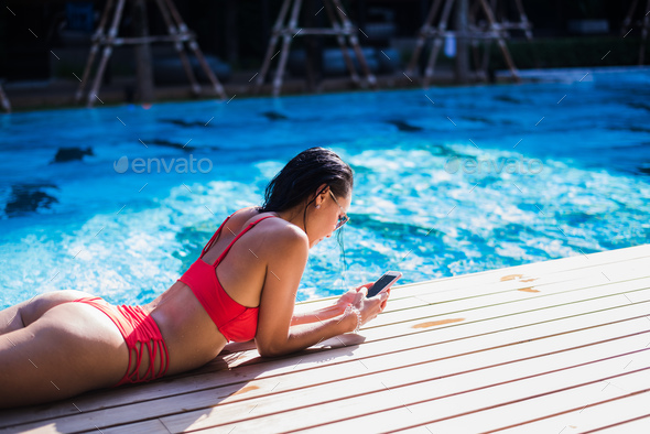 Beautiful woman leaning on poolside and typing a text message on cellphone - Stock Photo - Images