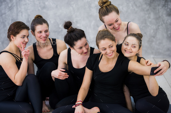 Group of women sitting and relaxing after a long yoga class and taking selfie - Stock Photo - Images