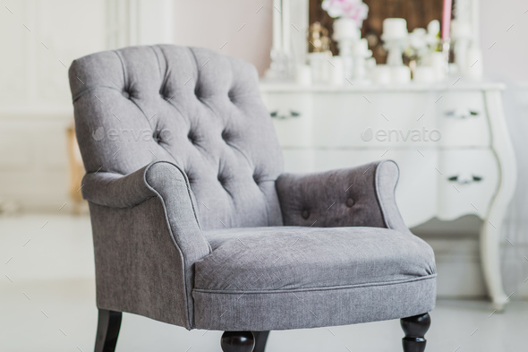 beige color upholstered chair in living room with flowers - Stock Photo - Images