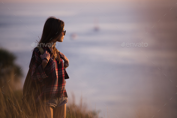 Woman traveler looks at the edge of the cliff on the sea bay of mountains in the background at - Stock Photo - Images