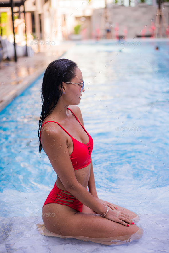 Spending hot summer day poolside. Beautiful young woman in red bikini relaxing by the pool. - Stock Photo - Images