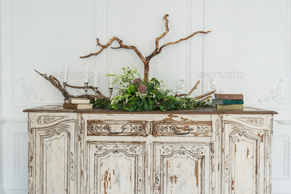 White ancient vintage commode with plants and handmade wool decoration - Stock Photo - Images