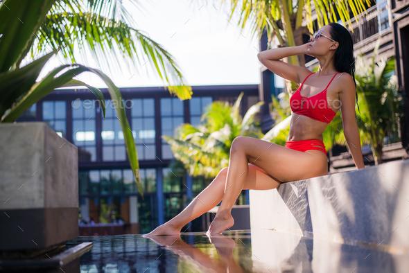Beautiful slim sexy woman wearing red bikini relax near outdoor water pool on resort - Stock Photo - Images