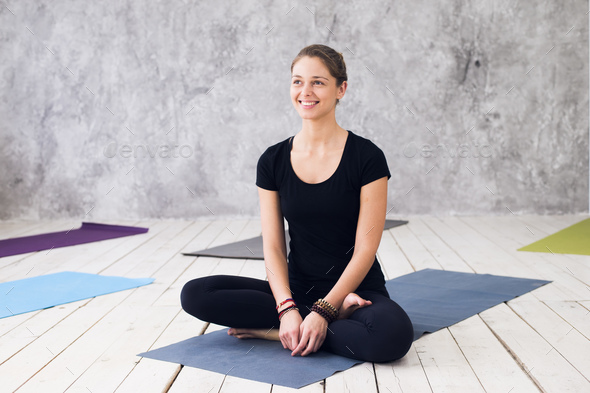 Woman practicing meditation at a yoga studio - Stock Photo - Images