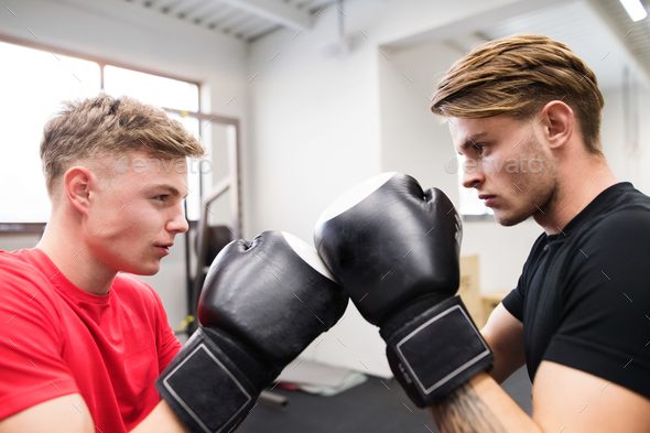 Two fit handsome men in gym boxing. - Stock Photo - Images