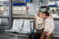 Senior couple waiting on train station, sitting on bench, kissin