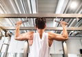 Hispanic man in gym doing pull-ups on horizontal bar.