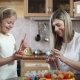 Beautiful mother and daughter painting eggs in the kitchen for Easter - VideoHive Item for Sale