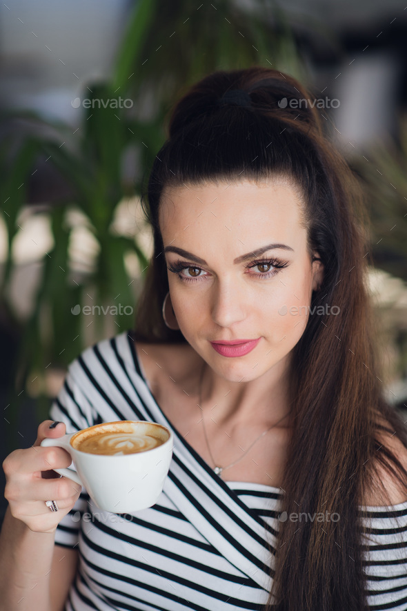 Closeup portrait of a woman in a cafe holding a cup of coffee or cappuccino. - Stock Photo - Images
