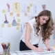 Fashion Designer Draws Sketches for a New Collection and Smiles Sweetly