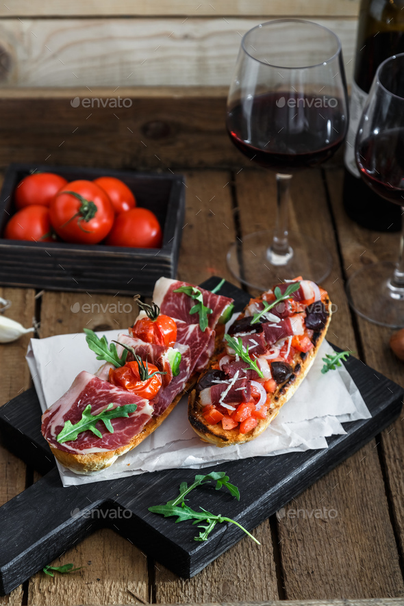 Spanish tapas with slices jamon serrano, salami, olives and cheese cubes on a wooden table. - Stock Photo - Images