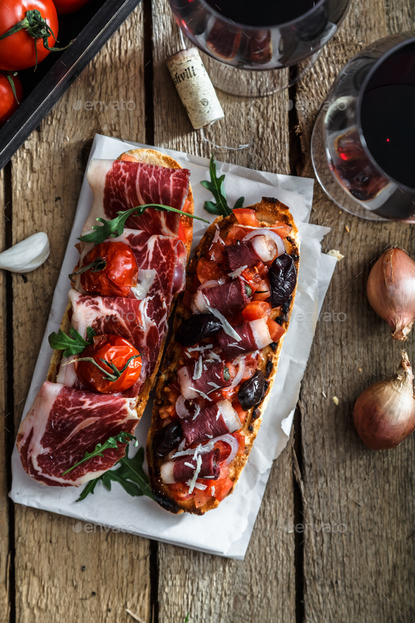 Variety of small sandwiches with jamon, tomatoes, parmesan cheese, fresh basil served with wine - Stock Photo - Images