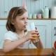 Adorable Little Girl Drinking Orange Juice on Breakfast on Morning, Small Child Drink, Fruits on