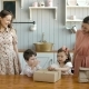Happy Twins Moms and His Little Daughter Girl and Boy Child Opening Box on Kitchen