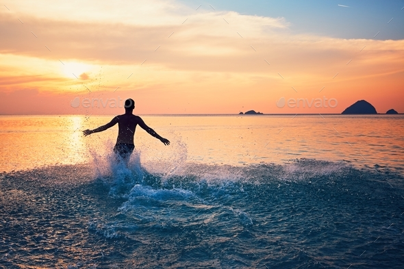 Man running into the sea - Stock Photo - Images