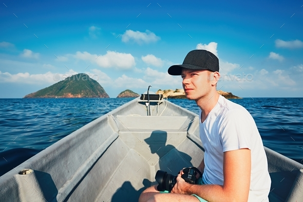 Photographer traveling by boat - Stock Photo - Images