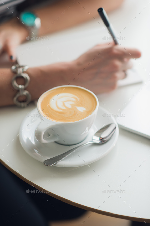 Hands writing on a paper in a notebook. Cup of cappuccino. Laptop nearby. - Stock Photo - Images