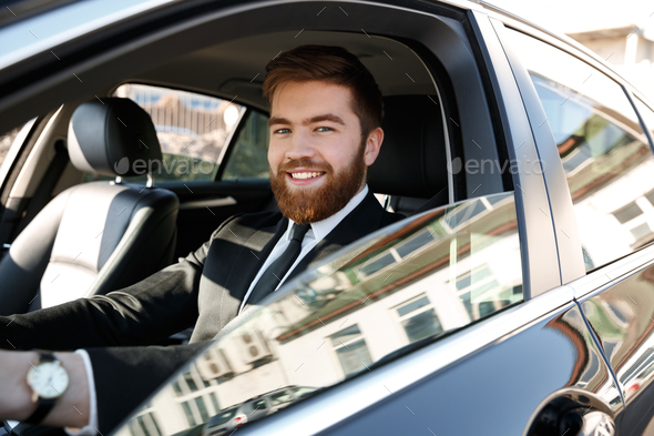 Side view of Smiling business man driving car - Stock Photo - Images