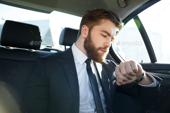 Confident young businessman looking at his watch - Stock Photo - Images