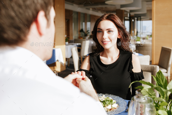 Smiling loving couple sitting in restaurant indoors - Stock Photo - Images