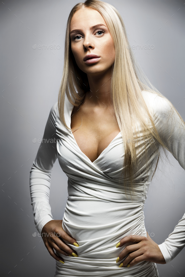 Confident fashion portrait of a blonde woman in white dress - Stock Photo - Images