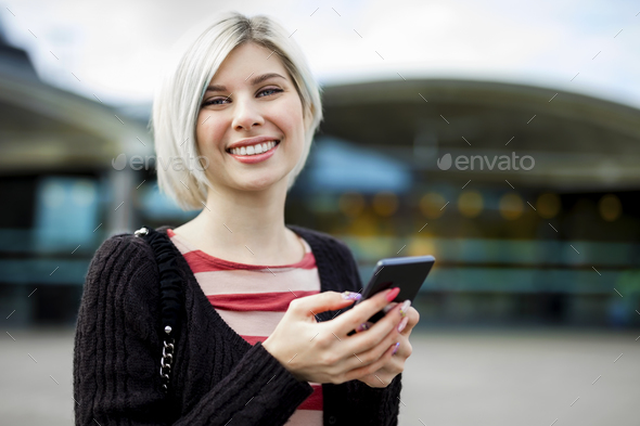 Woman Smiling While Using Mobile Phone Outside Train Station - Stock Photo - Images