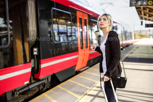 Woman With Luggage Standing At Train Station - Stock Photo - Images
