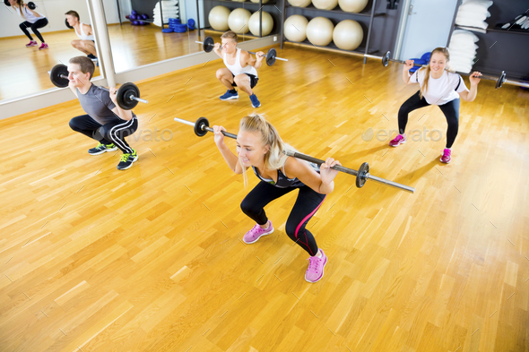 Friends in Group Lifting Barbell Rods In Fitness Gym - Stock Photo - Images