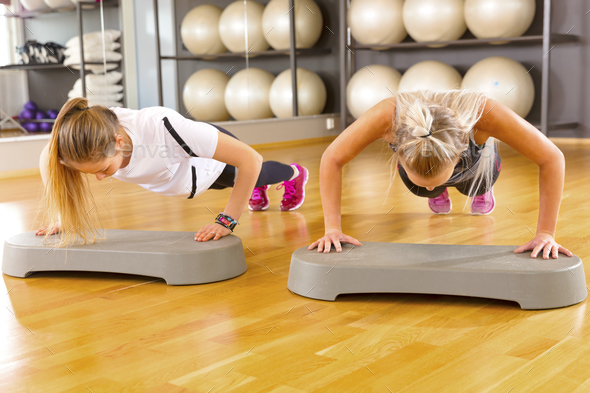 Two Confident Female Friends Doing Pushups In Gym - Stock Photo - Images