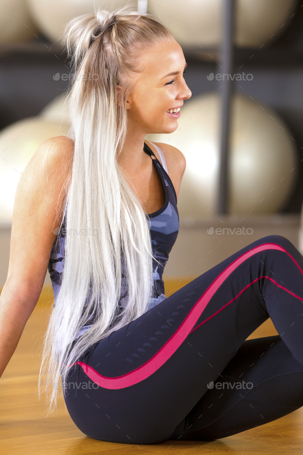 Smiling fitness woman sitting in workout outfit at the gym - Stock Photo - Images