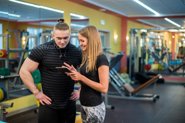 Fit attractive young couple at a gym looking at a tablet-pc as they monitor their progress and - Stock Photo - Images