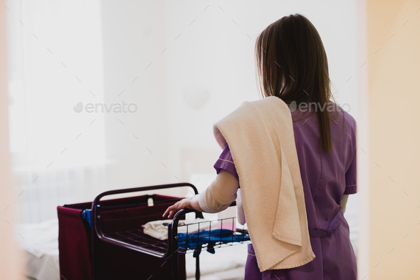 Young Female Maid pushing cart While Cleaning Hotel Rooms - Stock Photo - Images