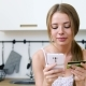 Attractive Lady with Cellphone and Bank Plastic Card at Kitchen