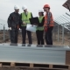 Engineers with Blueprint and Laptop on Solar Farm