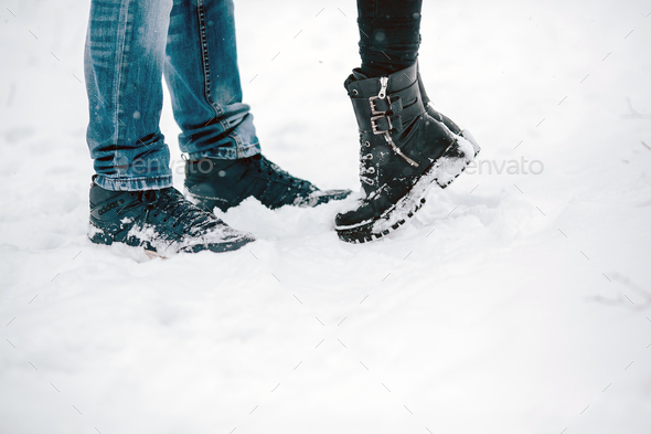 legs embracing couples standing on the snow - Stock Photo - Images