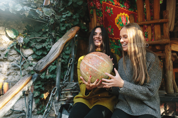 Two girls hold in hands a pumpkin - Stock Photo - Images