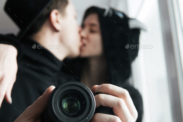 man and woman in black clothes kissing - Stock Photo - Images
